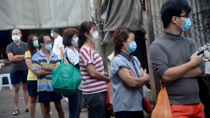 Residents wearing face mask line up outside a wet market during the movement control order due to the outbreak of the coronavirus disease (COVID-19) outside of Kuala Lumpur, Malaysia, on Wednesday, Ma