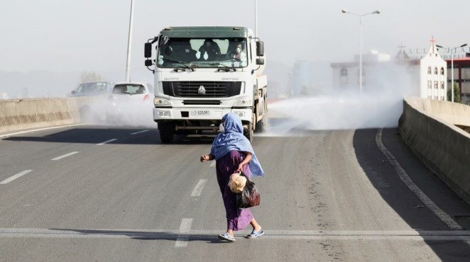 A woman wearing a face mask, runs in front of a truck spraying disinfectant on the street as part of measures to prevent the potential spread of coronavirus (COVID-19), in Addis Ababa, Ethiopia March