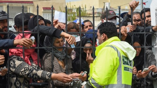 Impoverished Tunisian citizens gather with their identification cards in front of the headquarters of Mnihla delegation, in Ariana