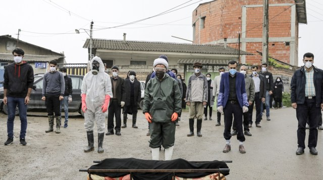 Mourners wearing protective clothing, face masks and gloves, pray over the body of a victim who died after being infected with the new coronavirus, in the outskirts of the city of Babol, in north of I