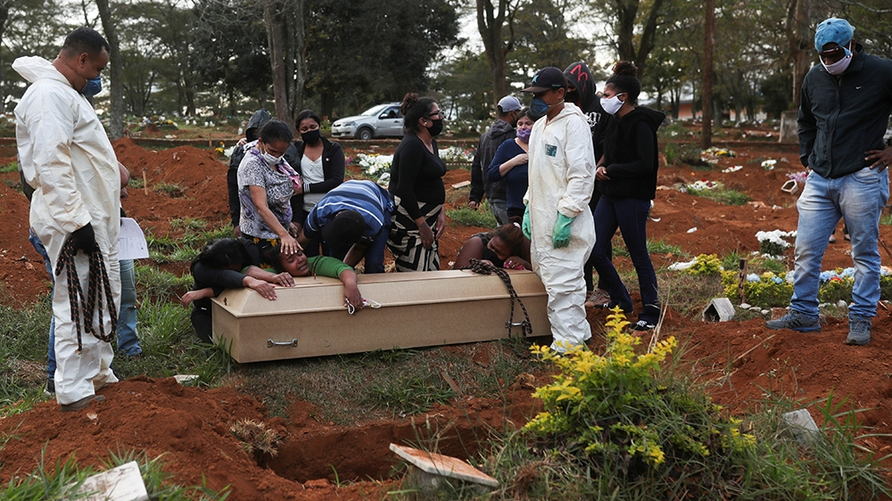 Relatives react during the burial of 64-year-old Raimunda Conceicao Souza, who died from the coronavirus disease (COVID-19), at Vila Formosa cemetery, Brazil's biggest cemetery, in Sao Paulo, Brazil