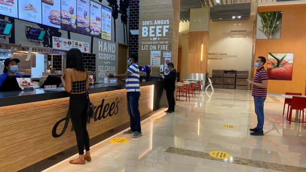 People wearing protective face masks order food as they keep social distancing at the food court in Dubai mall after the UAE government eased a curfew and allowed stores to open