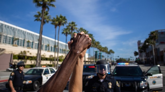 A black man and a white woman hold their hands up in a front of police officers in downtown Long Beach on May 31, 2020 during a protest against the death of George Floyd, an unarmed black man who died