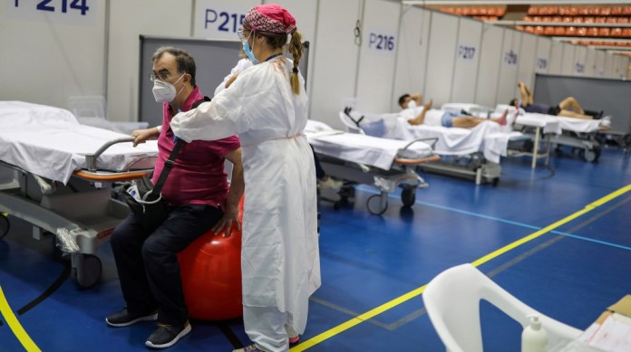 Daniel Catey, 62, a recovered COVID-19 patient, undergoes rehabilitation with a physical therapist at the Hospital Vall d'Hebron facility, a hastily converted sports centre, in Barcelona, Spain, June