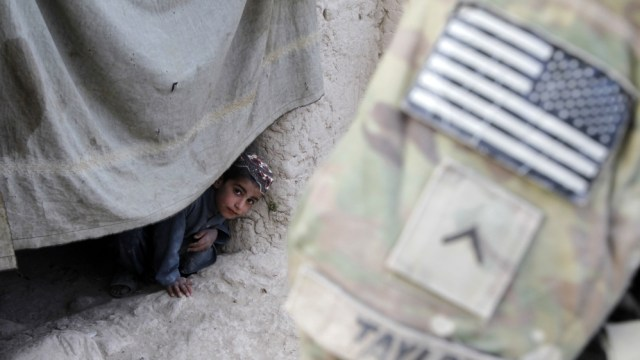 An Afghan boy watches a U.S. soldier on patrol in Zharay district in Kandahar province, southern Afghanistan