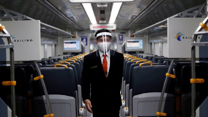 An employee wearing a protective mask and face shield walks inside a Railink train following the coronavirus disease (COVID-19) outbreak in Jakarta