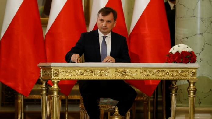 Zbigniew Ziobro signs documents after being designated as Minister of Justice, at the Presidential Palace in Warsaw