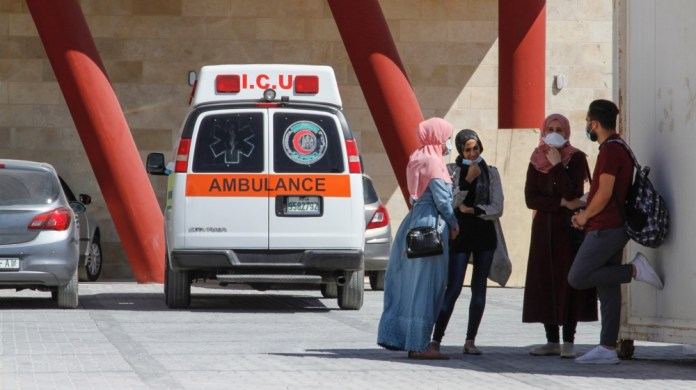 A group of nurses prepare to leave the Dura Hospital after the end of their shift.