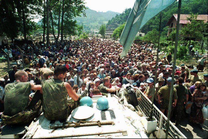 July 13, 1995 file photo, Dutch U.N. peacekeepers sit on top of an armored personnel carrier as Muslim refugees from Srebrenica, eastern Bosnia, gather in the nearby village of Potocari. A Dutch appea