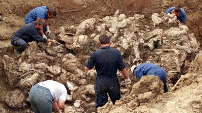 International forensic experts examine dozens of bodies in a mass grave in Pilice, September 18, 1996. Bosnia will mark the 25th anniversary of the massacre of more than 8,000 Bosnian Muslim men and b