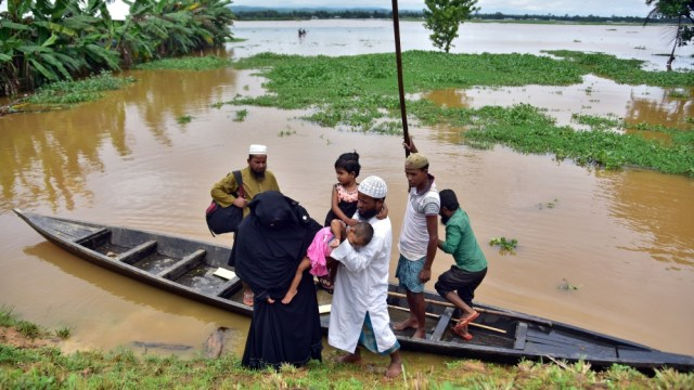 Flood-affected villagers disembark a boat after they reached a safer place at Kachua village
