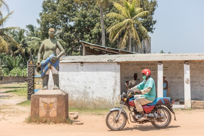 A man on a motorcycle rides past the statute in front of the Zomachi memorial square in Ouidah. As Western cities see statues of slaveholders and colonialists toppled, Benin's coastal town of Ouidah is going the other way, restoring monuments to the painful era of the slave trade. [Yanick Folly/AFP]