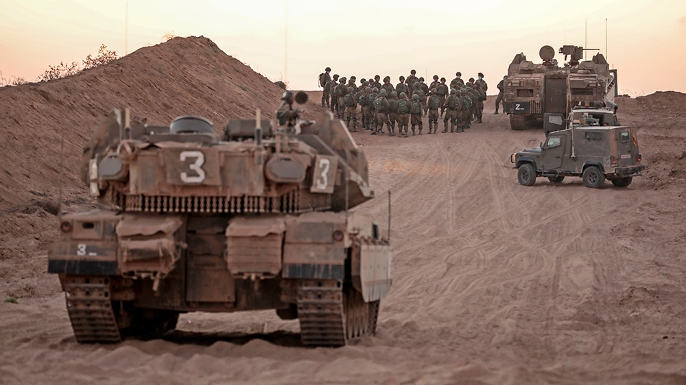 Israeli infantry soldiers gather next to tanks and an armoured personnel carrier near the Israeli border with the Gaza Strip, on August 16, 2020. (Photo by MENAHEM KAHANA / AFP)