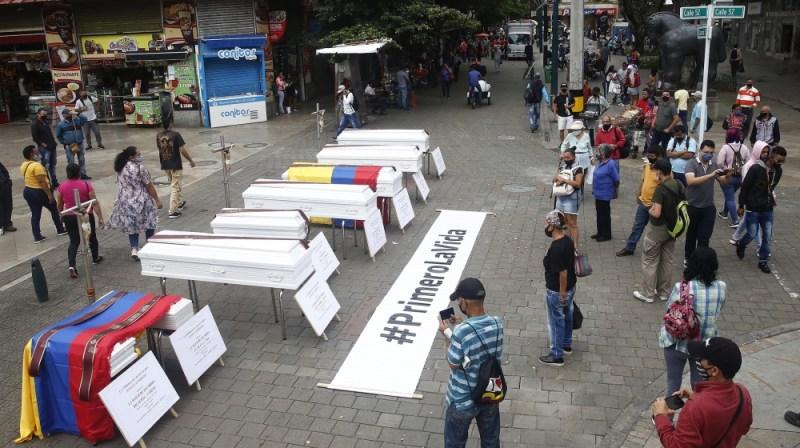 24 اگست 2020 کو ، میدیلن ، کولمبیا میں ، ملک میں حالیہ قتل عام کو مسترد کرنے کے ایک علامتی عمل کے طور پر کچھ شہری گلیوں میں رکھے تابوتوں کو دیکھ رہے ہیں۔ سول تنظیموں نے اس کام کو انجام دیا۔