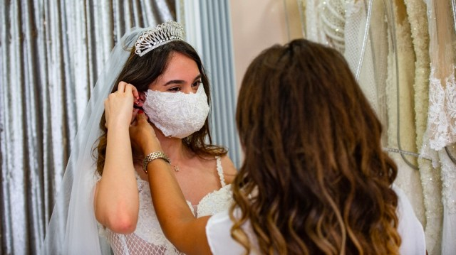 TURKEY-HEALTH-VIRUS-WEDDING-FASHION Wedding Dress designer Pinar Bent (back) adjusts a mannequin wearing a wedding dress with matching protective mask in her store in Istanbul, on June 30, 2020.
