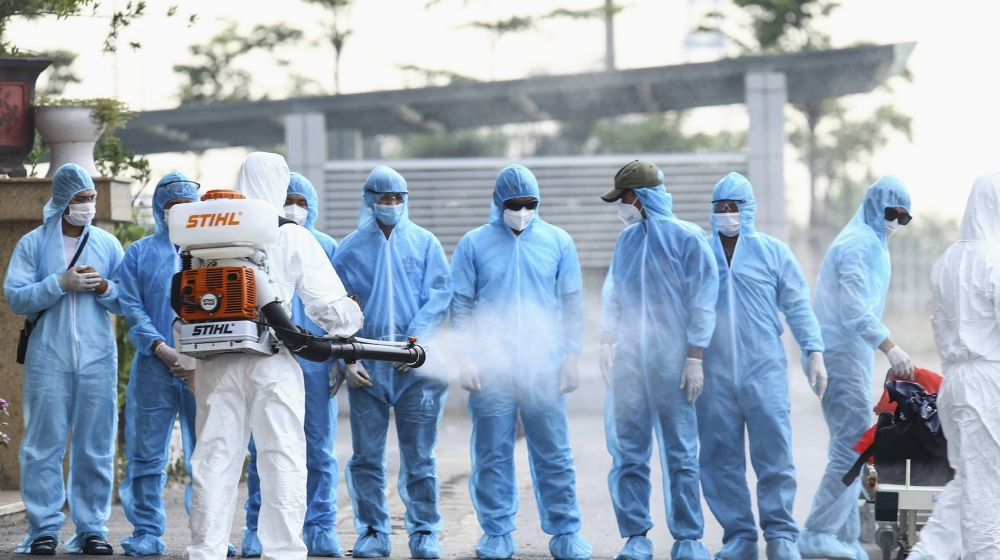 A health worker disinfects arriving Vietnamese COVID-19 patients at the national hospital of tropical diseases in Hanoi, Vietnam on Wednesday, July 29, 2020. The 129 patients who were working in Equat