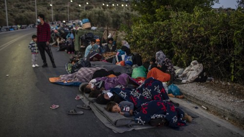 Migrants sleep on the road near the Moria refugee camp on the northeastern island of Lesbos, Greece, Thursday, Sept. 10, 2020. A second fire in Greece's notoriously overcrowded Moria refugee camp dest