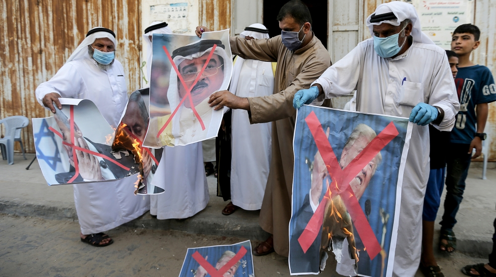 Palestinians burn pictures depicting U.S. President Donald Trump, Israeli Prime Minister Benjamin Netanyahu and Bahrain's King Hamad bin Isa Al Khalifa during a protest against Bahrain?s move to norma