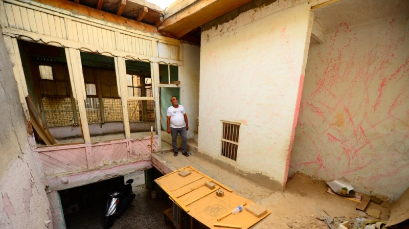 Aysser Al Ameri stands in a house he recently purchased in Baghdad's old Shewake neighborhood. It features old Baghdadi architectural features, including an inner court yard and wooden balcony called