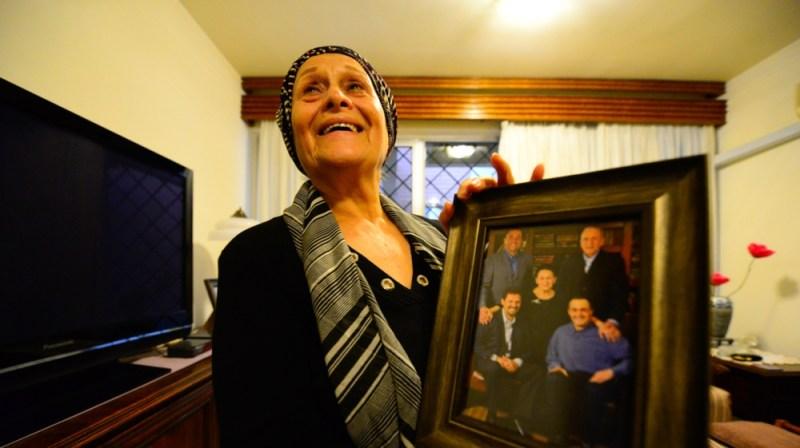 Hind Jameel holds up an old family photo inside her house in Baghdad's Harthiya neighborhood. All of her three adult sons have left Iraq.    [Haider Hamdani/Al Jazeera]