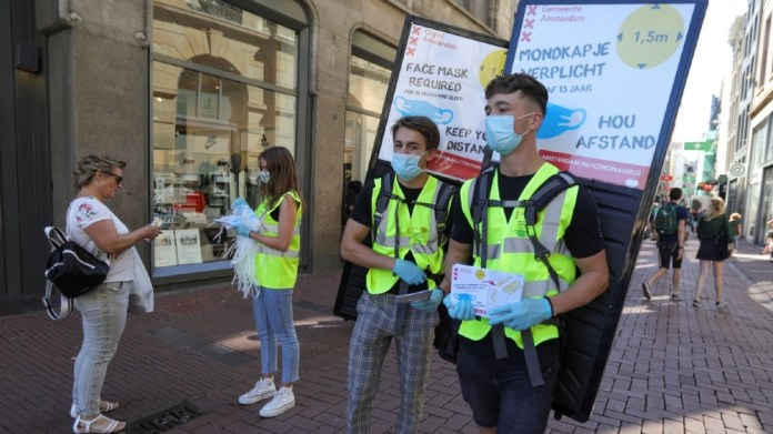 People wearing yellow vests hand out masks and information brochures where to wear the mandatory masks in the busiest streets of the city, during the coronavirus disease (COVID-19) outbreak,