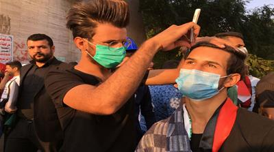 A  barber trimming hair at a protest site in Baghdad