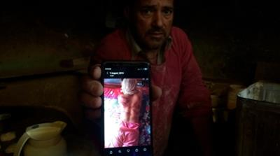In this Monday, Aug. 26, 2019, photo, a Kashmiri baker Sonaullah Sofi displays a photograph of his son after he was allegedly tortured by Indian army soldiers at their bakery in the southern village o