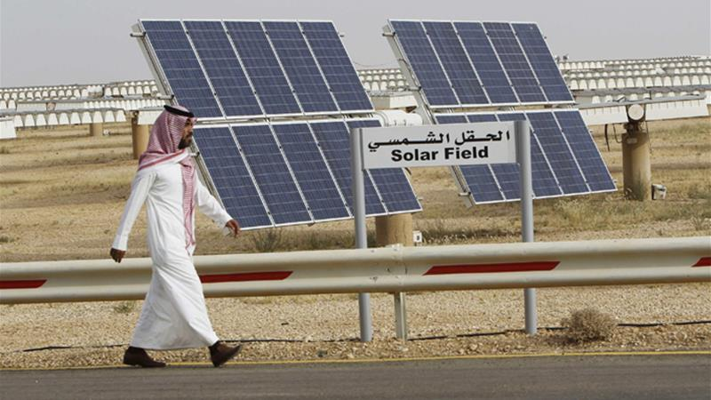 A Saudi man walks on a street past a field of solar panels at the King Abdulaziz city of Sciences and Technology, Al-Oyeynah Research Station, May 21, 2012 [Reuters]