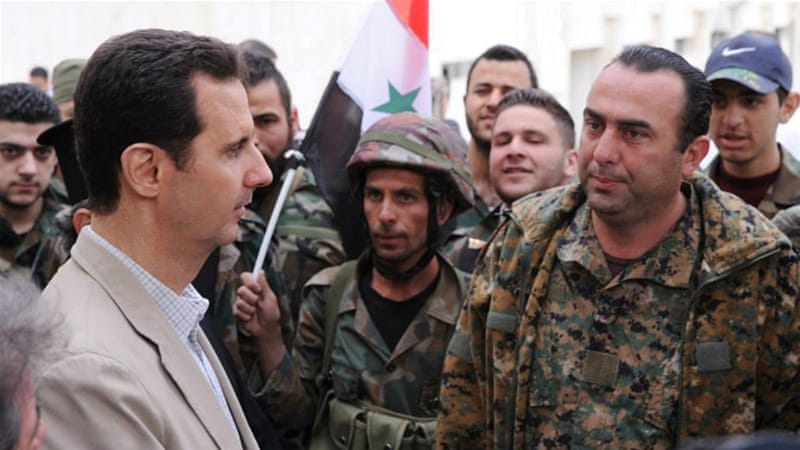 Assad talks to government soldiers during his visit to the Christian village of Maaloula, near Damascus [AP]