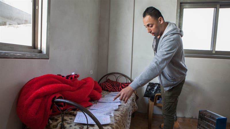 Nour Alyan, 27, who says he was held in stress positions for hours while in Israeli detention, displays the paperwork from his five separate arrests [Edmee Van Rijn/Al Jazeera]