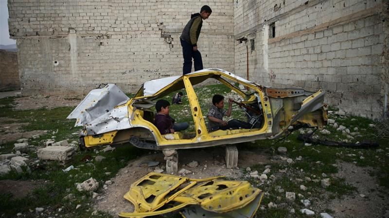 Boys play on a wrecked car in the besieged city of Douma, one of the areas hardest hit by the siege of Eastern Ghouta. [Bassam Khabieh/Reuters]