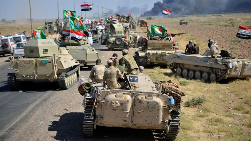 Shia Popular Mobilisation Forces (PMF) and Iraqi army members gathered on the outskirts of Hawija [Reuters]