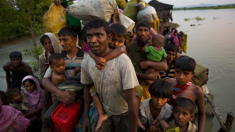 Rohingya Muslims carry their children and belongings after crossing the border from Myanmar into Bangladesh in November [The Associated Press]