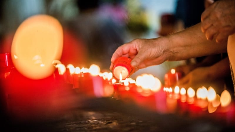 A Roma pilgrim lights a candle during the annual festival held in the Catholic chapel of Szentkut in Csatka, Hungary, September 2016 [Zoltan Balogh/EPA]