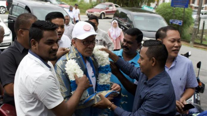 Supporters drape a garland around Anwar Ibrahim as he campaigns to return to parliament in Malaysia [Kate Mayberry/Al Jazeera]