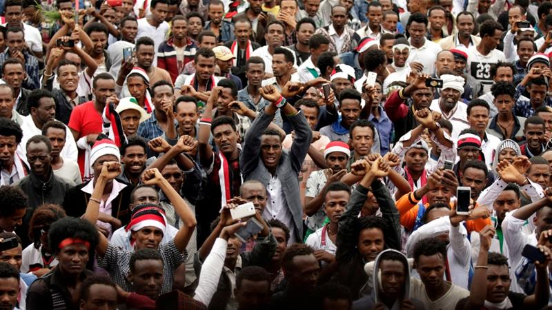 Demonstrators chant slogans while flashing the Oromo protest gesture, in Bishoftu town, Ethiopia [Tiksa Negeri/Reuters]