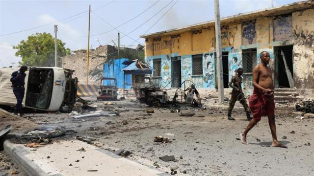 A man walks from the scene of a suicide car bombing near Somalia's presidential palace in Mogadishu [Feisal Omar/Reuters]