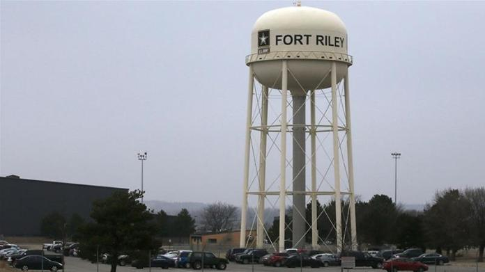 Vehicles park around a water tower at Fort Riley, Kansas [FIle: Orlin Wagner/AP Photo]