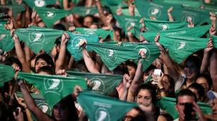 Activists hold green handkerchiefs - the symbol of the abortion rights movement. Argentina's president is backing a bill to legalise the procedure [File:Agustin Marcarian/Reuters]