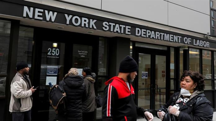People gather at the entrance for the New York State Department of Labor offices in Brooklyn; the office is closed to the public as part of measures to stop the spread of COVID-19 measures that have spawned a record number of layoffs in the US [File: Andrew Kelly/Reuters]