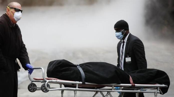 A funeral director wears personal protective equipment due to COVID-19 concerns while collecting a body at The Brooklyn Hospital Center in New York [File: John Minchillo/AP Photo]
