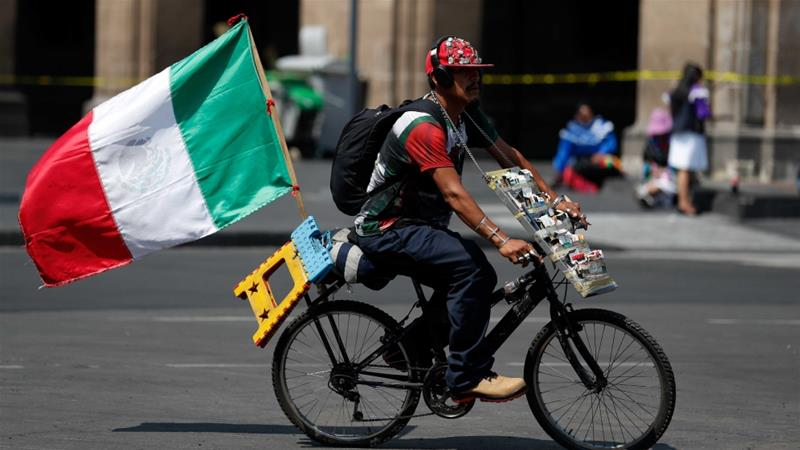 A man who sells loose cigarettes rides a bike with a Mexican flag attached, as he passes roped-off government buildings in the Zocalo, Mexico City's main square [Rebecca Blackwell/AP Photo]