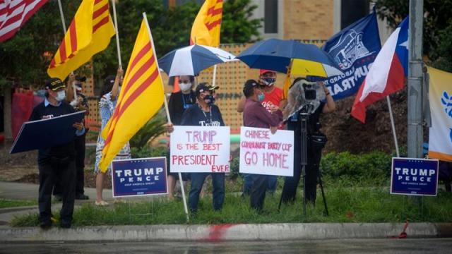Protesters hold up signs and flags outside the Chinese consulate in Houston, US [Mark Felix/AFP]