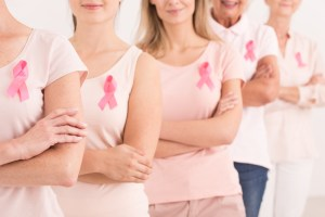 women together with pink shirts and pink ribbons for breast cancer awareness
