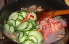 Adaugati in tigaie ardeiul gras si castravetele verde si gatiti 2-3 minute, amestecand din cand in   cand, pana ce se evapora apa lasata de legume.