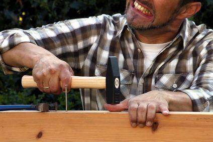 Man hits thumb with hammer
