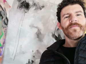 artist allanisart standing with his black and white abstract painting
