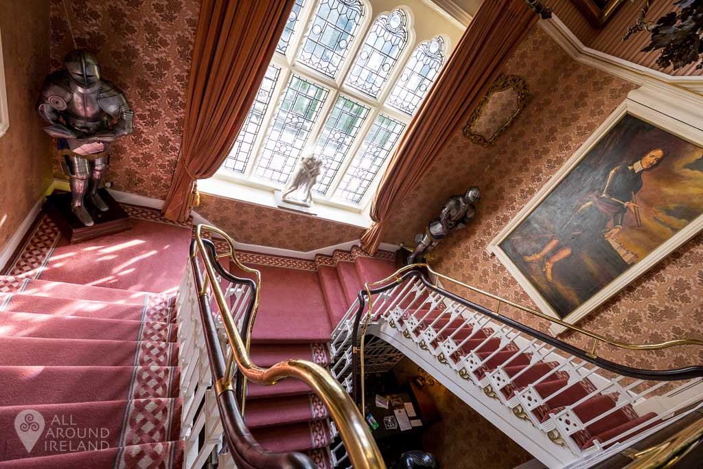 The main staircase at Cabra Castle, complete with suit of armour.