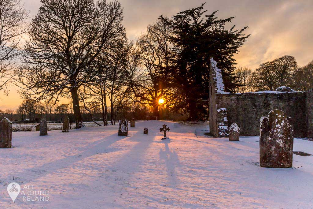 The setting sun casts long shadows of the gravestones by the ruins of the Abbey