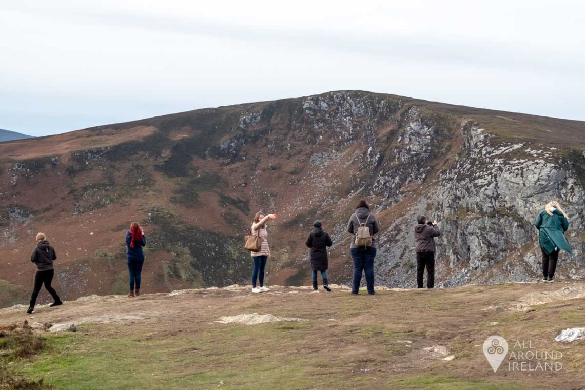 A row of people lined up to photograph the views at Lough Tay in Wicklow